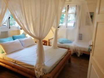 """Chambre """"Bambou"""" avec grand lit double plus lit simple d'appoint. Moustiquaires. Climatisation."""