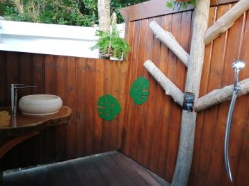 Le must de Bwa Majorelle! Sa douche tropicale conçue à ciel ouvert avec des bois locaux dont un Tendacayou et un Bois d'Inde. Lavabo en pierre et support en bois rouge Courbaril.